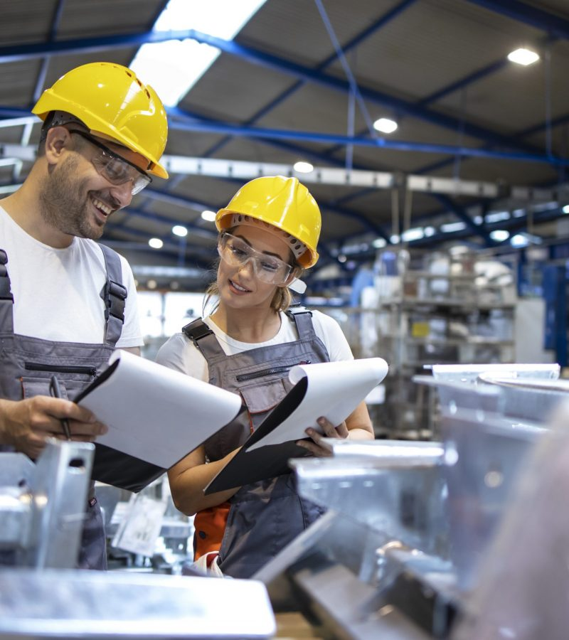 Factory workers analyzing production results in large industrial hall.